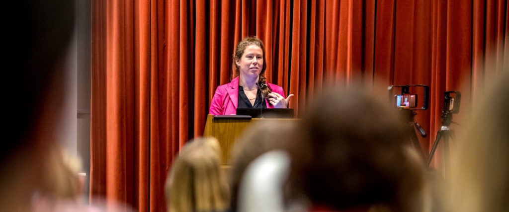 A woman behind a podium on stage giving a talk to to a room of people