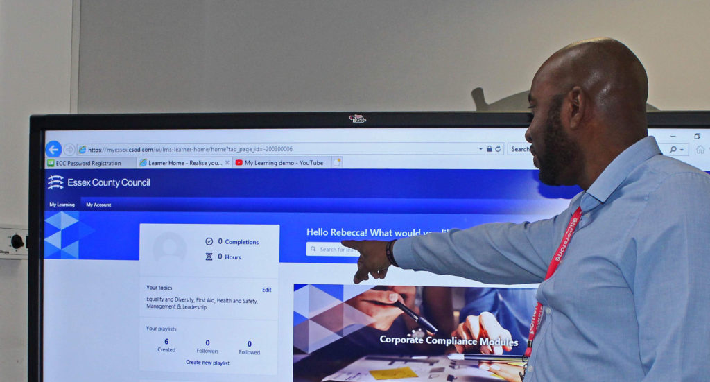 Man pointing to a television with the Essex Council Learning website on the screen