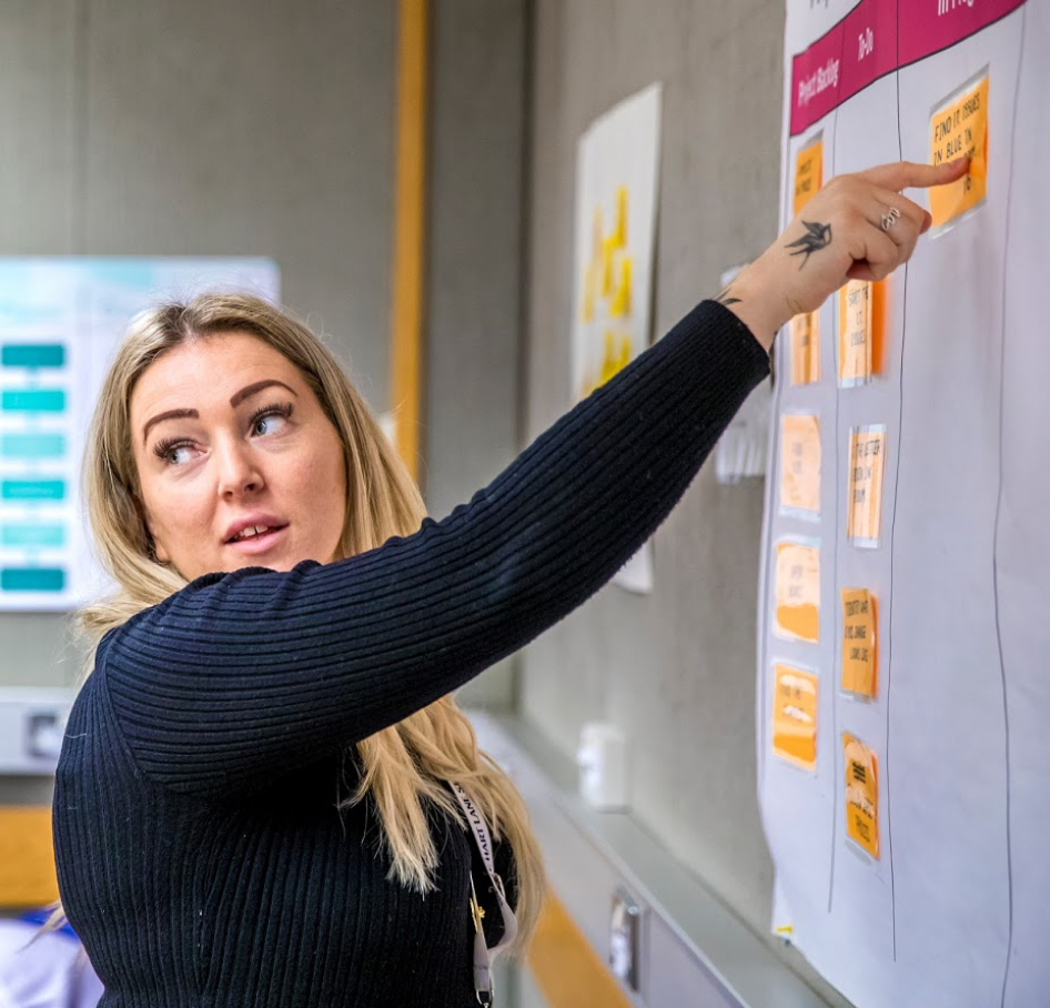 Female pointing to a sticky note on a wall