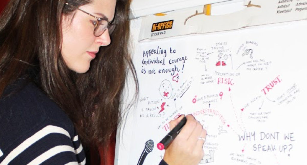 A woman writing sketch notes on a Stick Pad with a red pen
