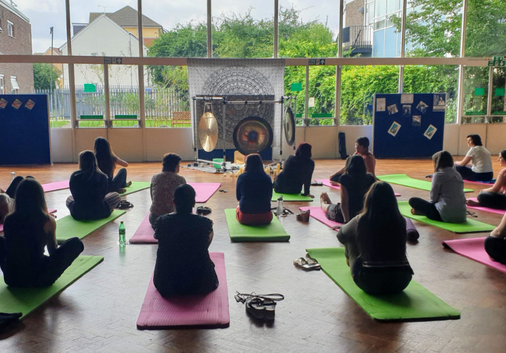 A group of people sitting on Yoga mats at a wellbeing event